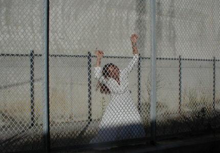 La ragazza nel sogno con l'abito bianco si appoggia ad una rete.
